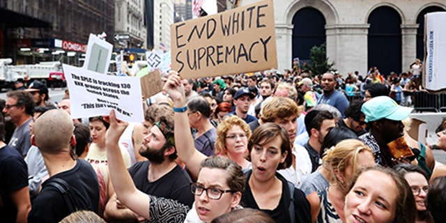 Protesters wave anti-racism signs during protests in front of Trump Tower in New York City, New York, U.S., August 14, 2017.