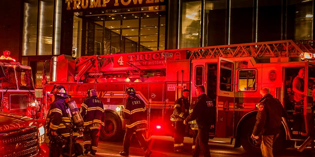 Firefighters work outside Trump Tower in New York City, April 7, 2018.