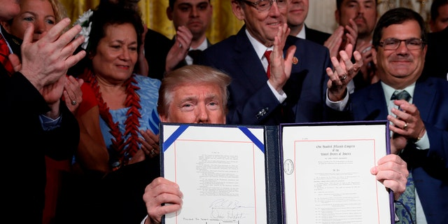 "U.S. President Donald Trump displays the ""VA Accountability Act"" during a signing ceremony  in the East Room of the White House in Washington, U.S., June 23, 2017. REUTERS/Jonathan Ernst - RTS18DQB"