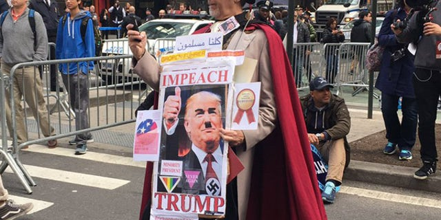 A man dressed in a top hat and cape wears a picture of President Trump with an Adolf Hitler-style mustache.
