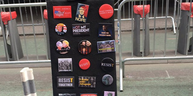 """Anti-President Trump buttons were for sale at the """"I Am A Muslim Too"""" rally."""