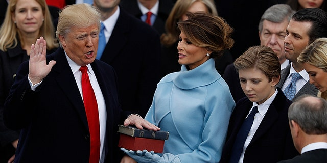 Donald Trump takes the oath of office as his wife Melania holds a Bible and his son Barron looks on during his inauguration as the 45th president of the United States on the West front of the U.S. Capitol in Washington, U.S., January 20, 2017.