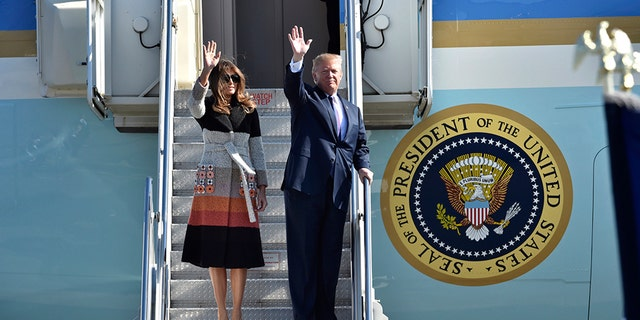 President Donald Trump and first lady Melania Trump wave from the steps of Air Force One.