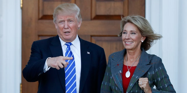 President Trump and Education Secretary Betsy DeVos are seen at Trump National Golf Club Bedminster in Bedminster, N.J., prior to Trump taking office, in an undated photo. (Associated Press)