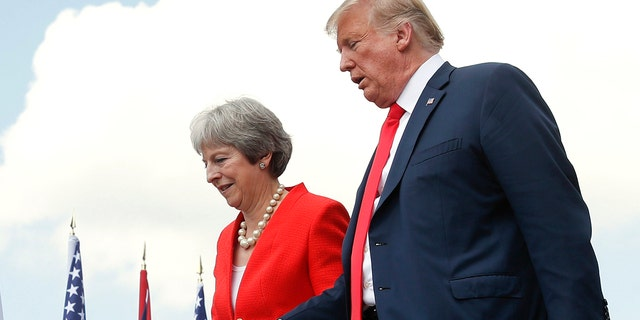 President Donald Trump and British Prime Minister Theresa May hold hands at the conclusion of their joint news conference at Chequers, in Buckinghamshire, England, Friday, July 13, 2018.