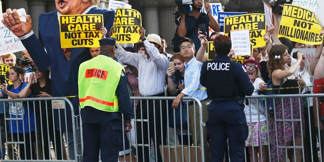 Protesters gather outside the Trump International Hotel in Washington, Wednesday, June 28, 2017, as President Donald Trump arrives at the hotel for fundraiser. (AP Photo/Manuel Balce Ceneta)
