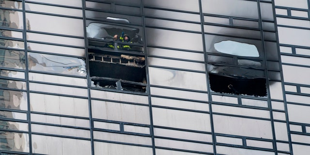 A firefighter looks out from the window of a fire damaged apartment in Trump Tower in New York on Saturday, April 7, 2018.