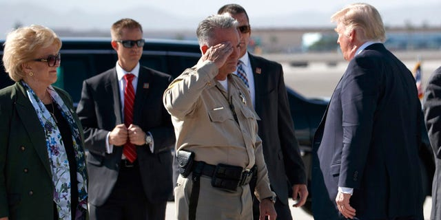 Clark County Sheriff Joseph Lombardo salutes President Donald Trump after he arrived at Las Vegas McCarran International Airport to meet with victims and first responders of the mass shooting.