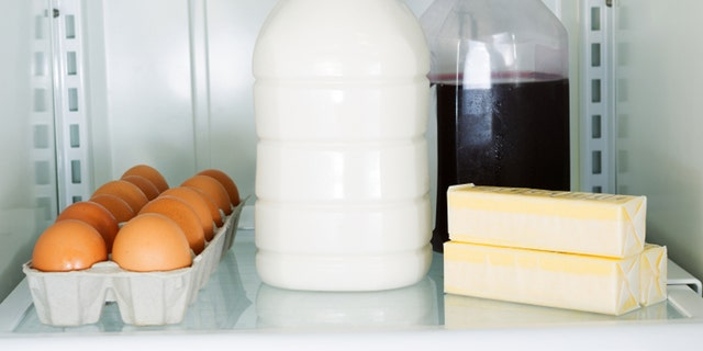 Horizontal photo of milk, eggs, butter and juice on glass shelf inside of refrigerator
