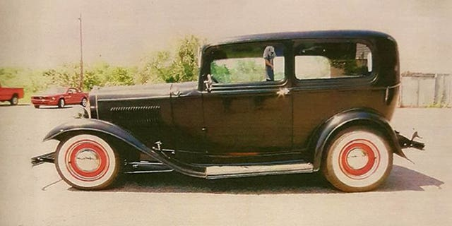 The black coupe has a red interior, undercoating, grille and wheels.