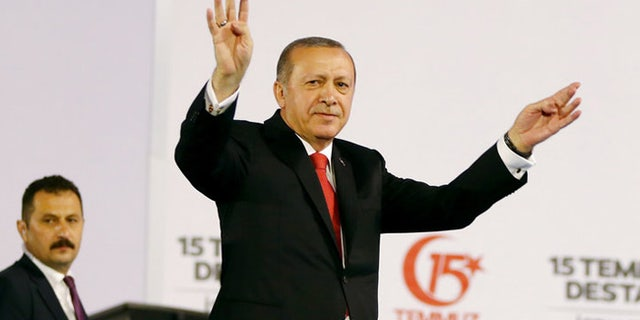 Turkey's President Recep Tayyip Erdogan accompanied by his wife Emine waves to his supporters as he arrives to commemorate the one year anniversary of the July 15, 2016 failed coup attempt, in Istanbul, Saturday, July 15, 2017. Turkey commemorates the first anniversary of the July 15 failed military attempt to overthrow Erdogan, with a series of events honouring some 250 people, who were killed across Turkey while trying to oppose coup-plotters. (Presidency Press Service via AP, Pool)