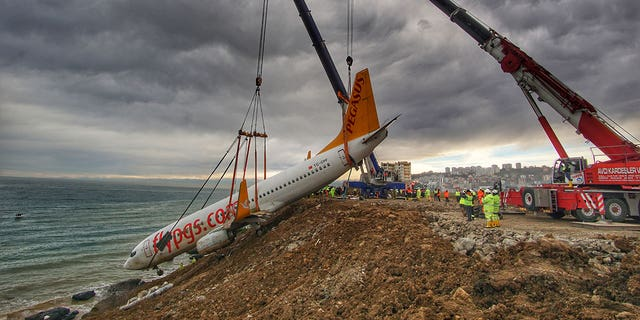 Turkish authorities used a large crane to lift a passenger plane from the side of the cliff on Thursday.