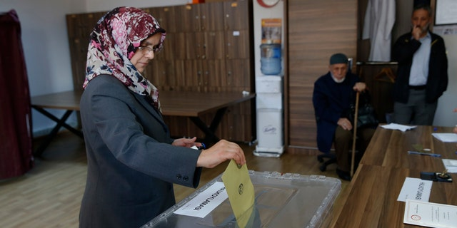 A woman casts a ballot inside a polling station in Istanbul, Sunday, April 16, 2017. Voters in Turkey were deciding Sunday on the future of their country, with polling stations opening for a historic referendum, which was called by President Recep Tayyip Erdogan, on whether to approve reforms that would concentrate power in the hands of the president. (AP Photo/Lefteris Pitarakis)