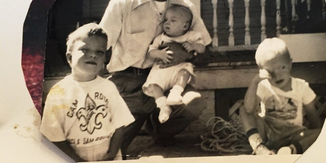 In an old photograph, Francis Turner poses with his three sons, each diagnosed with Down syndrome.