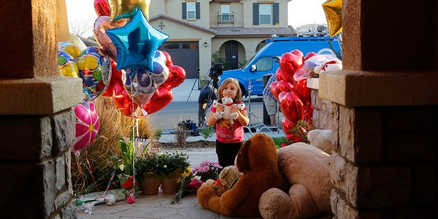 Jan. 18, 2018: Neighbor Rilee Unger, 3, plays with a toy after dropping off a couple of her own teddy bears on the porch of a home where police arrested a couple on Sunday accused of holding 13 children captive in Perris, Calif.
