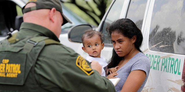 A mother migrating from Honduras holds her 1-year-old child as surrendering to U.S. Border Patrol agents after illegally crossing the border near McAllen, Texas.