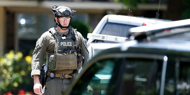 State and federal law enforcement officers in tactical gear work outside a home in Alvin, Texas, as part of the investigation in the aftermath of a deadly shooting at Santa Fe High School.