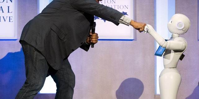 File photo: Astrophysicist Neil deGrasse Tyson interacts with Pepper, a social humanoid robot developed by Aldebaran for SoftBank, during the Clinton Global Initiative's annual meeting in New York, September 28, 2015. (REUTERS/Lucas Jackson)