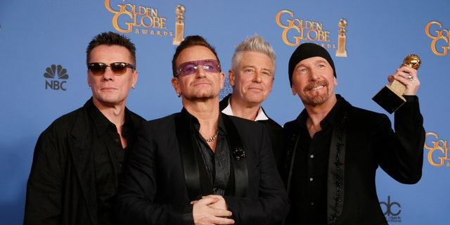 """January 12, 2014. Adam Clayton, Bono, Larry Mullen, Jr., and The Edge (L to R), from the band U2, pose backstage with their award for Best Original Song for """"Ordinary Love"""" from the film """"Mandela: Long Walk to Freedom"""" at the 71st annual Golden Globe Awards in Beverly Hills, California."""