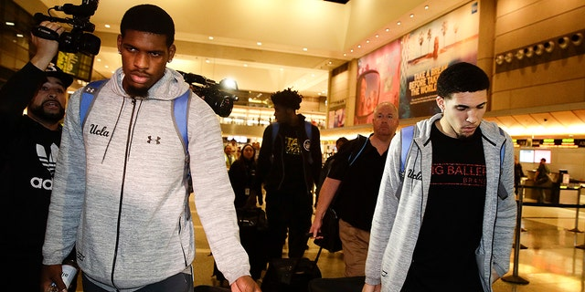 UCLA basketball players Cody Riley (left), LiAngelo Ball (right), and Jalen Hill (background center), are surrounded by the media as they leave the Los Angeles International Airport.