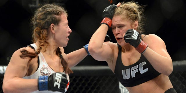 Dec 28, 2013; Las Vegas, NV, USA;    Ronda Rousey (red gloves) and Miesha Tate (blue gloves) fight during their UFC women's bantamweight championship bout at the MGM Grand Garden Arena. Mandatory Credit: Jayne Kamin-Oncea-USA TODAY Sports - RTX16W96