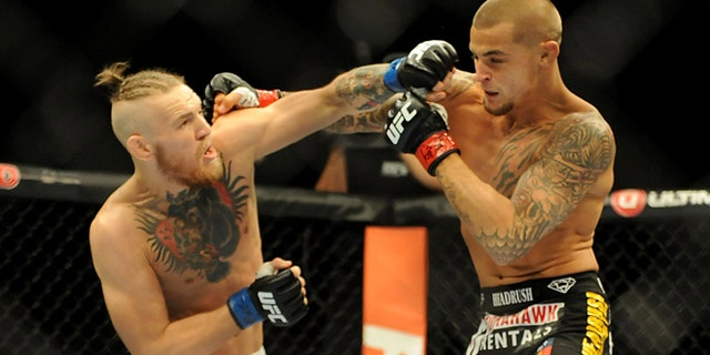Sep 27, 2014; Las Vegas, NV, USA; Conor McGregor (blue gloves) fights Dustin Poirier (red gloves) during a featherweight fight during UFC 178 at MGM Grand Garden Arena. Mandatory Credit: Stephen R. Sylvanie-USA TODAY SportsBEST QUALITY AVAILABLE - RTR47ZES