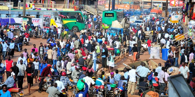 In this Saturday Oct. 1, 2011 photo, people gather at a bus terminal in Kampala, Uganda.