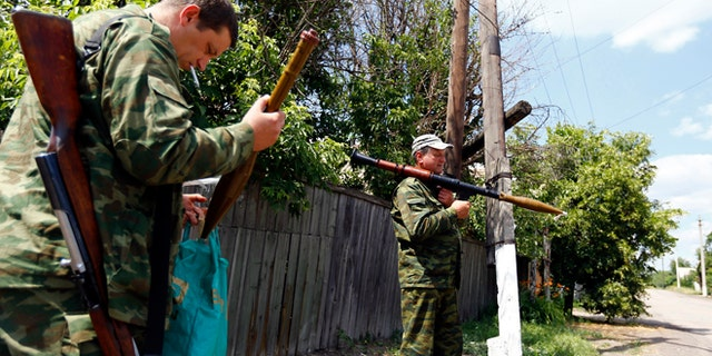 June 19, 2014: Armed pro-Russian separatists stand guard in Seversk, located near the town of Krasny Liman, Donetsk region. Ukrainian troops and pro-Russian separatists were locked in fierce fighting in the east of Ukraine on Thursday after rebels rejected a call to lay down their arms in line with a peace plan proposed by President Petro Poroshenko, government forces said.