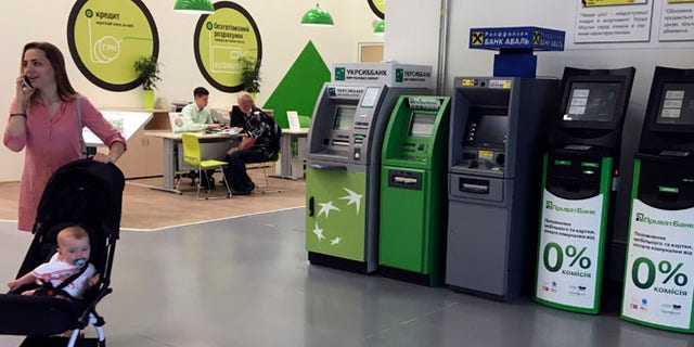A woman passes by cash machines that do not work in a city supermarket in Kiev, Ukraine, Wednesday, June 28, 2017.  The cyberattack ransomware that has paralyzed computers across the world hit Ukraine hardest Tuesday, with victims including top-level government offices, energy companies, banks, cash machines, gas stations, and supermarkets.  (AP Photo/Efrem Lukatsky)