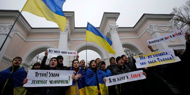 """March 11, 2014: People hold Ukrainian flags and banners that read: """"Putin! Take away the green men"""", """"They got me married without me being there"""", """"Referendum is a step to war"""", during a rally against the breakup of the country in Simferopol, Crimea, Ukraine."""