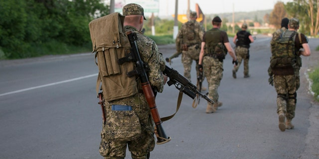 May 17, 2014: Pro-Russian militants walk to their positions to fight against Ukrainian government troops at a checkpoint blocking the major highway which links Kharkiv, outside Slovyansk, eastern Ukraine.