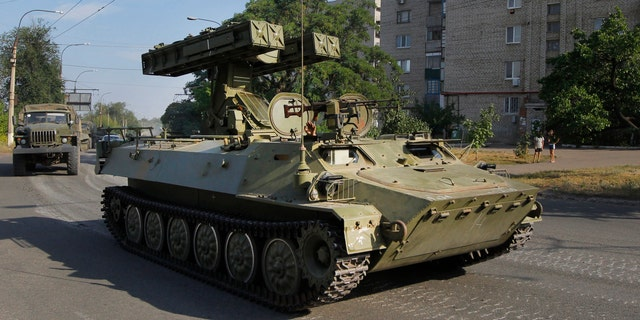 FILE - In this is Sunday, Aug. 17, 2014 file photo, a pro-Russian missile launcher drives in the town of Krasnodon. (AP Photo/Sergei Grits, File)