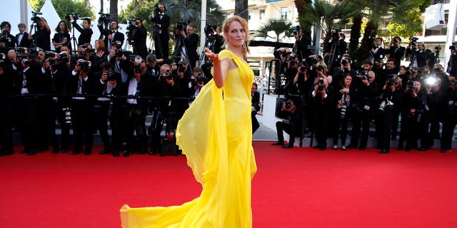 """May 23, 2014. Uma Thurman poses on the red carpet as she arrives for the screening of the film """"Sils Maria"""" (Clouds of Sils Maria) in competition at the 67th Cannes Film Festival in Cannes."""