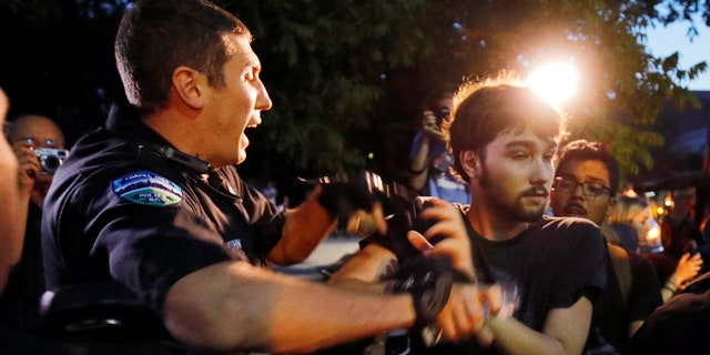 Police struggle with a protester during unrest at a demonstration against a statue of a Confederate soldier nicknamed Silent Sam on the campus of the University of North Carolina in Chapel Hill, North Carolina, U.S. August 22, 2017. REUTERS/Jonathan Drake - RC1596B5E160