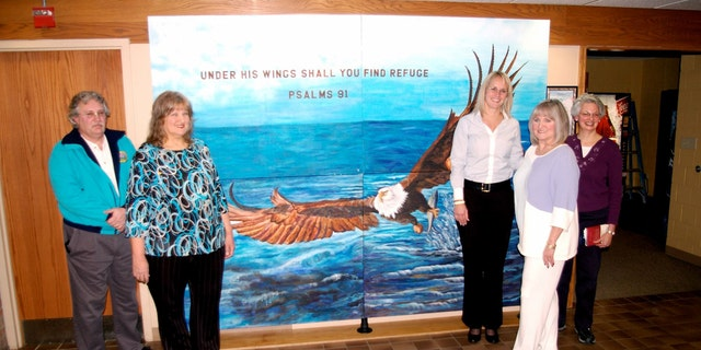 """Fred Lewallen, left, Nancy Cupp, Mayor Lydia Mihalik, Judi Herrin, and Cathy Schock in front of the """"Under His Wings"""" mural in Findlay's municipal building."""