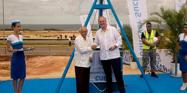 Unilever CEO Paul Polman, right, and Cuba's Minister of Industries Salvador Pardo, pose for photos after laying a cornerstone for a new business center, in Mariel, Cuba, Friday, Nov. 4, 2016. The Dutch consumer product giant has become one of the largest foreign companies to move into a special economic development zone at the Cuban port of Mariel that is meant to jumpstart outside investment on the island. (Ismael Francisco/Cubadebate via AP)