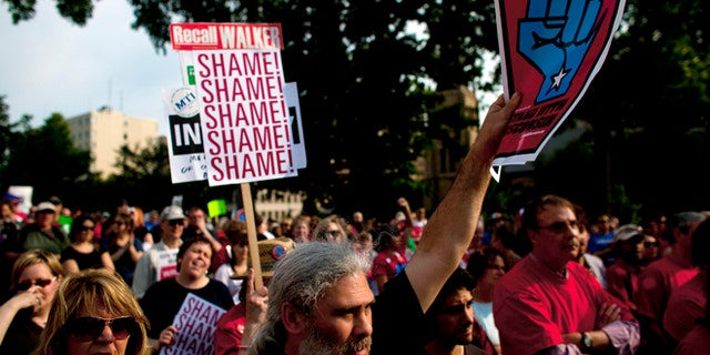 In this June 14, 2011, file photo, protesters demonstrate against controversial legislation curbing union power in Madison, Wis.