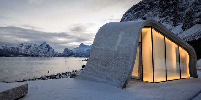 The wave-shaped concrete bathroom offers a view of the open Norwegian Sea.