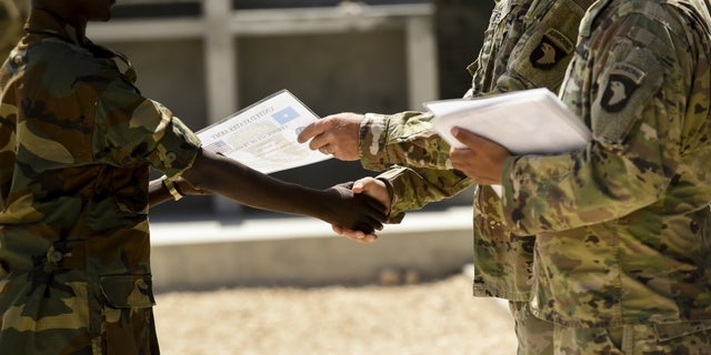 Soldiers from the U.S. Army's 101st Airborne Division present certificates of training completion to Somali National Army soldiers during a graduation ceremony May 24, 2017, in Mogadishu Somalia.