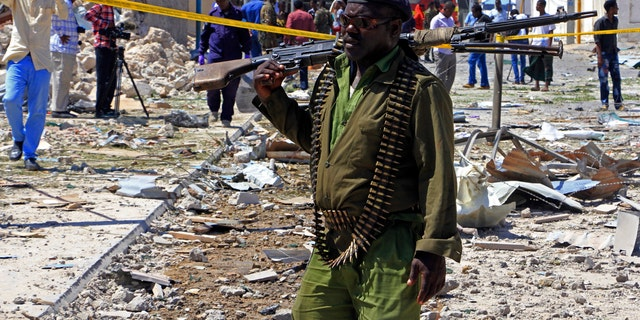 FILE - In this Jan. 2, 2017, file photo, a Somali soldier patrols the area of a suicide car bomb attack in Mogadishu, Somalia.