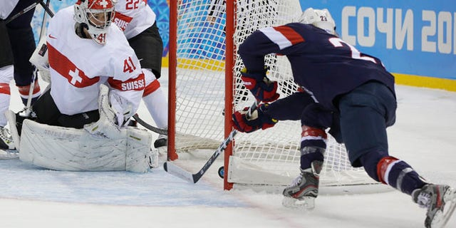 Feb. 10, 2014: Goalkeeper Florence Schelling of Switzerland watches as Amanda Kessel of the Untied States shoot slides in for the goal during the first period of the 2014 Winter Olympics women's ice hockey game at Shayba Arena in Sochi, Russia.