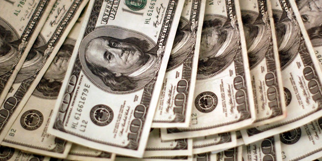 Four thousand U.S. dollars are counted out by a banker counting currency at a bank.