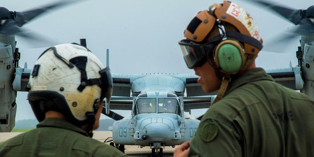 U.S. Marine Corps Cpl. Brandon Guico, a Marine Medium Tiltrotor Squadron 262 airframe aerial observer, and William Payne, a VMM-262 avionics technician, watch a MV-22 Osprey takeoff at Misawa Air Base, Japan last month.