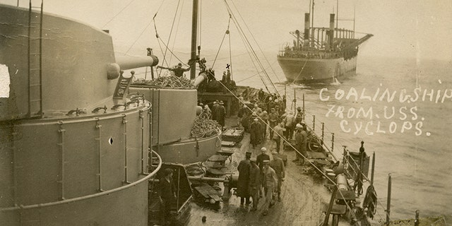 The USS Cyclops, in the background, transferring bags of coal with the USS South Carolina in 1914.