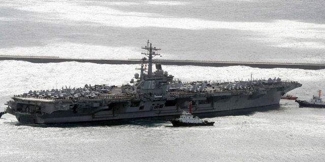 The aircraft carrier USS Ronald Reagan is escorted into Busan port, South Korea, after completing a joint drill.