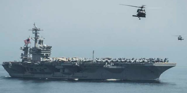 Helicopters fly from the aircraft carrier USS Theodore Roosevelt, which is headed to the Korean Peninsula.