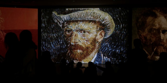 "File photo - Visitors look at a projection of Vincent Van Gogh's painting ""Self-Portrait with Grey Felt Hat"" at the ""Van Gogh Alive"" exhibition in Athens, Greece, November 10, 2017. Picture taken Nov. 10, 2017. (REUTERS/Alkis Konstantinidis)"
