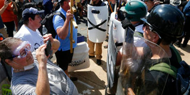 Counter demonstrators photograph white supremacists at the entrance to Emancipation Park in Charlottesville, Va., on Aug. 12, 2017.
