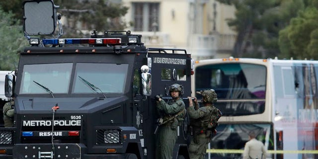 Las Vegas SWAT officers leave the scene of a stand-off in a bus along Las Vegas Boulevard, Saturday, March 25, 2017, in Las Vegas. Las Vegas police said the gunman in a fatal shooting on the Strip who barricaded himself inside a public bus has surrendered peacefully after shutting down the busy tourism corridor for hours.  (AP Photo/John Locher)