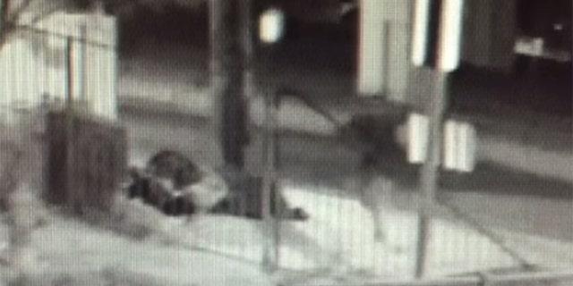 The shooter, right, is seen walking toward homeless men sleeping on the sidewalk.
